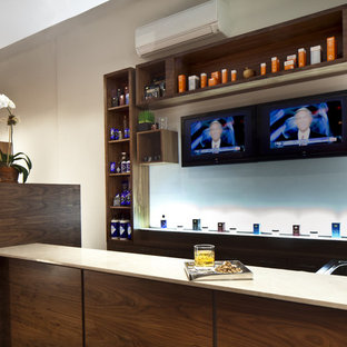 Seated home bar - large modern u-shaped seated home bar idea in New York with solid surface countertops and beige countertops