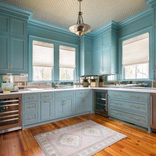 チャールストンのミッドセンチュリースタイルのおしゃれなウェット バー (ドロップインシンク、インセット扉のキャビネット、青いキャビネット、クオーツストーンカウンター、ミラータイルのキッチンパネル、濃色無垢フローリング、茶色い床、白いキッチンカウンター) の写真