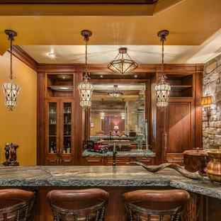 フェニックスのサンタフェスタイルのおしゃれな着席型バー (ガラス扉のキャビネット、中間色木目調キャビネット、ミラータイルのキッチンパネル) の写真
