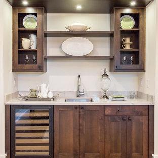 シアトルの地中海スタイルのおしゃれなウェット バー (I型、アンダーカウンターシンク、シェーカースタイル扉のキャビネット、濃色木目調キャビネット、白いキッチンカウンター) の写真