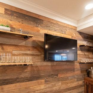 Foto di un grande angolo bar con lavandino stile rurale con lavello da incasso, ante con finitura invecchiata, top in legno, paraspruzzi marrone, paraspruzzi in perlinato, pavimento grigio e top marrone
