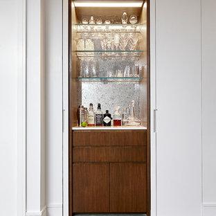 Imagen de bar en casa lineal, contemporáneo, pequeño, sin pila, con armarios con paneles lisos, encimera de cuarzo compacto, salpicadero con efecto espejo, suelo de madera clara, suelo gris y puertas de armario de madera oscura