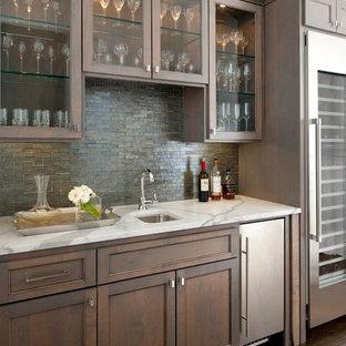 ダラスのトラディショナルスタイルのおしゃれなウェット バー (濃色無垢フローリング、I型、アンダーカウンターシンク、落し込みパネル扉のキャビネット、濃色木目調キャビネット、グレーのキッチンパネル、ボーダータイルのキッチンパネル、茶色い床、白いキッチンカウンター) の写真