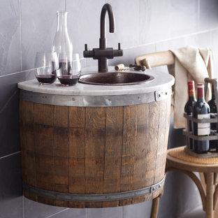 Design ideas for an industrial home bar in San Luis Obispo with a built-in sink, freestanding cabinets, dark wood cabinets, marble worktops, black splashback and slate splashback.