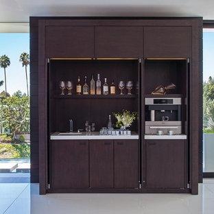 Стильный дизайн: прямой домашний бар в современном стиле с мойкой, плоскими фасадами и темными деревянными фасадами - последний тренд