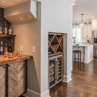 Ispirazione per un piccolo angolo bar american style con top in legno, paraspruzzi nero, paraspruzzi in ardesia, pavimento in legno massello medio, pavimento marrone e top marrone
