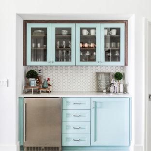 ビーチスタイルのおしゃれなホームバー (I型、落し込みパネル扉のキャビネット、青いキャビネット、白いキッチンパネル、モザイクタイルのキッチンパネル、グレーの床、白いキッチンカウンター) の写真