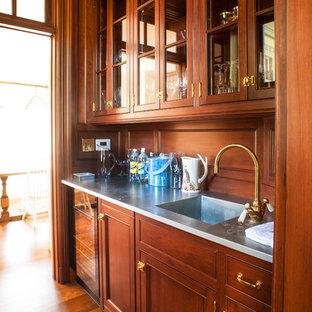 ポートランド(メイン)の小さいヴィクトリアン調のおしゃれなウェット バー (ll型、一体型シンク、シェーカースタイル扉のキャビネット、濃色木目調キャビネット、ステンレスカウンター、茶色いキッチンパネル、木材のキッチンパネル、無垢フローリング、茶色い床) の写真