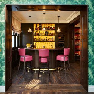 Exemple d'un bar de salon linéaire victorien de taille moyenne avec des tabourets, un placard avec porte à panneau encastré, des portes de placard en bois sombre, un plan de travail en bois, une crédence jaune, une crédence en feuille de verre, un sol en bois foncé, un sol marron et un plan de travail marron.