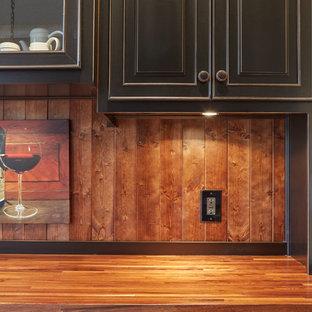 アトランタの小さい地中海スタイルのおしゃれなウェット バー (I型、アンダーカウンターシンク、レイズドパネル扉のキャビネット、黒いキャビネット、木材カウンター、茶色いキッチンパネル、淡色無垢フローリング) の写真