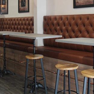 Esempio di un bancone bar industriale di medie dimensioni con nessun'anta, ante in legno scuro, top in laminato e pavimento in linoleum