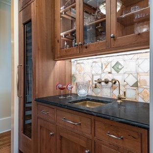 ワシントンD.C.の小さいトランジショナルスタイルのおしゃれなウェット バー (ll型、アンダーカウンターシンク、中間色木目調キャビネット、オニキスカウンター、マルチカラーのキッチンパネル、ライムストーンのキッチンパネル、無垢フローリング、茶色い床、黒いキッチンカウンター) の写真