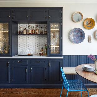 Modelo de bar en casa lineal, campestre, con armarios estilo shaker, puertas de armario azules, salpicadero multicolor, suelo de madera oscura y suelo marrón