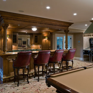 Photo of a large traditional galley breakfast bar in New York with a built-in sink, recessed-panel cabinets, medium wood cabinets, marble worktops, green splashback, stone slab splashback and carpet.