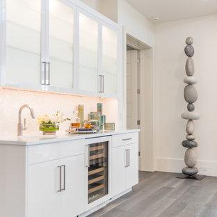 Ejemplo de bar en casa con fregadero lineal, costero, con puertas de armario blancas, salpicadero blanco, suelo de madera clara y encimeras blancas