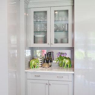 フィラデルフィアの小さいエクレクティックスタイルのおしゃれなホームバー (I型、ガラス扉のキャビネット、グレーのキャビネット、大理石カウンター、ミラータイルのキッチンパネル、無垢フローリング) の写真