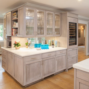 Inspiration for a large traditional l-shaped home bar in New York with recessed-panel cabinets, light wood cabinets, marble worktops and mirror splashback.