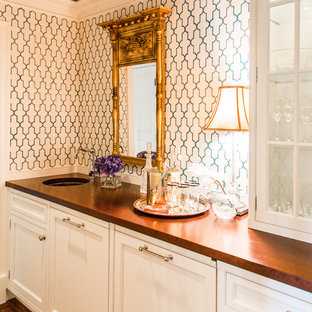 This is an example of a medium sized traditional single-wall wet bar in Boston with recessed-panel cabinets, white cabinets, wood worktops, multi-coloured splashback, medium hardwood flooring and a submerged sink.