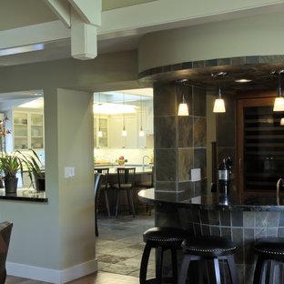 Immagine di un piccolo bancone bar tradizionale con lavello sottopiano, ante di vetro, ante in legno scuro, top in granito, paraspruzzi multicolore, paraspruzzi in ardesia, pavimento in legno massello medio e pavimento marrone