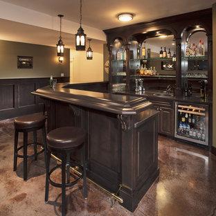 Idee per un bancone bar tradizionale di medie dimensioni con lavello da incasso, ante con bugna sagomata, ante in legno bruno, top in legno, paraspruzzi a specchio, pavimento in cemento e top marrone