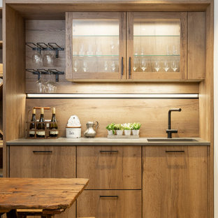 Photo of a contemporary single-wall wet bar in Sussex with glass-front cabinets, light wood cabinets, wood splashback, beige floors and grey worktops.