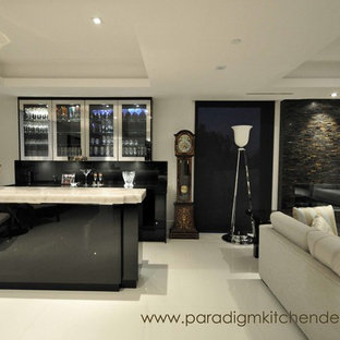This is an example of a medium sized contemporary galley wet bar in Vancouver with a submerged sink, flat-panel cabinets, black cabinets, marble worktops, black splashback, stone slab splashback and porcelain flooring.