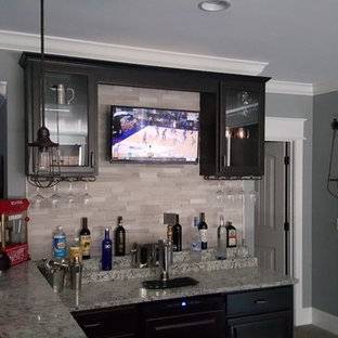 Seated home bar - mid-sized modern l-shaped ceramic floor seated home bar idea in Indianapolis with a drop-in sink, glass-front cabinets, dark wood cabinets, granite countertops, multicolored backsplash and ceramic backsplash