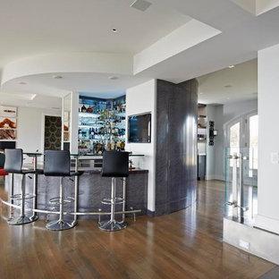 Immagine di un bancone bar minimalista di medie dimensioni con nessun'anta, top in vetro, paraspruzzi grigio e pavimento in legno massello medio