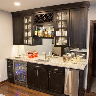 Idee per un grande armadio bar classico con lavello sottopiano, ante con riquadro incassato, top in granito, paraspruzzi a specchio, pavimento in laminato, pavimento marrone, top multicolore e ante grigie