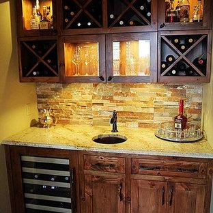 Ispirazione per un piccolo armadio bar stile rurale con lavello sottopiano, ante marroni, top in granito, paraspruzzi marrone, paraspruzzi con piastrelle in pietra e ante in stile shaker