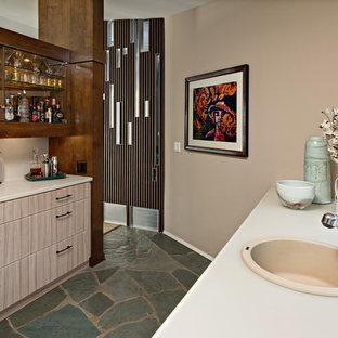 ミネアポリスの大きいコンテンポラリースタイルのおしゃれなウェットバー (ドロップインシンク、フラットパネル扉のキャビネット、ベージュのキャビネット、ガラスカウンター、ベージュキッチンパネル、ライムストーンの床、スレートの床、ターコイズの床) の写真