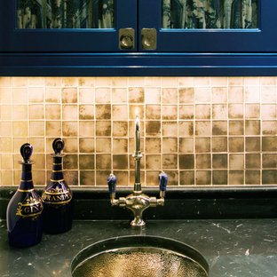 Inspiration for a traditional single-wall wet bar in New York with a submerged sink, glass-front cabinets, blue cabinets, marble worktops, mosaic tiled splashback and black worktops.