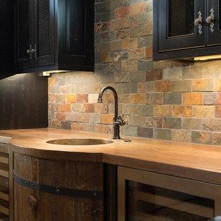 他の地域の中くらいのミッドセンチュリースタイルのおしゃれなウェット バー (I型、アンダーカウンターシンク、木材カウンター、黒いキャビネット、緑のキッチンパネル、スレートの床、スレートのキッチンパネル、茶色いキッチンカウンター、落し込みパネル扉のキャビネット) の写真