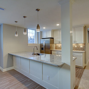 Photo of a large classic galley breakfast bar in Milwaukee with a built-in sink, recessed-panel cabinets, white cabinets, granite worktops, multi-coloured splashback, ceramic splashback and porcelain flooring.
