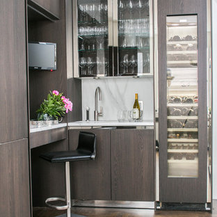 Inspiration for a small contemporary dark wood floor wet bar remodel in New York with glass-front cabinets and white backsplash