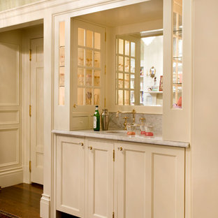 Small traditional single-wall wet bar in Boston with a submerged sink, recessed-panel cabinets, white cabinets and medium hardwood flooring.
