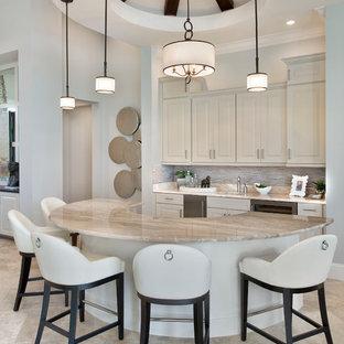 マイアミのトラディショナルスタイルのおしゃれな着席型バー (アンダーカウンターシンク、レイズドパネル扉のキャビネット、ベージュのキャビネット、マルチカラーのキッチンパネル、ベージュの床) の写真