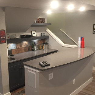 Mid-sized transitional single-wall medium tone wood floor and brown floor seated home bar photo in Denver with an undermount sink, gray cabinets, shaker cabinets, quartz countertops, brown backsplash and metal backsplash