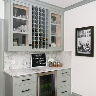 Photo of a small traditional single-wall wet bar in Other with glass-front cabinets, green cabinets, marble worktops, grey splashback, marble splashback, medium hardwood flooring, brown floors and grey worktops.