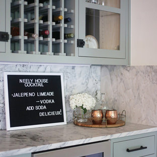 Inspiration for a small traditional single-wall wet bar in Other with glass-front cabinets, green cabinets, marble worktops, grey splashback, marble splashback, medium hardwood flooring, brown floors and grey worktops.