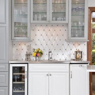 Esempio di un angolo bar con lavandino classico con ante di vetro, ante bianche, paraspruzzi bianco, top in acciaio inossidabile e pavimento bianco