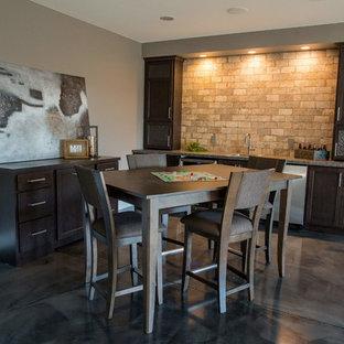 Ispirazione per un bancone bar classico di medie dimensioni con lavello da incasso, ante in stile shaker, ante in legno bruno, top in laminato, paraspruzzi beige, paraspruzzi in mattoni e pavimento in cemento