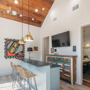 ヒューストンのトランジショナルスタイルのおしゃれなウェット バー (ll型、ルーバー扉のキャビネット、ヴィンテージ仕上げキャビネット、ベージュの床、緑のキッチンカウンター) の写真