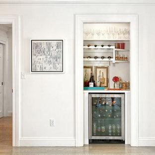 Modelo de bar en casa clásico renovado con armarios abiertos, puertas de armario blancas, suelo de madera clara y suelo beige