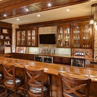 Foto di un grande bancone bar stile rurale con lavello da incasso, ante di vetro, ante in legno bruno, top in legno, paraspruzzi grigio, paraspruzzi con piastrelle in pietra, pavimento in gres porcellanato, pavimento marrone e top marrone