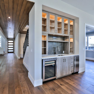 This is an example of a large modern l-shaped home bar in San Francisco with shaker cabinets, white cabinets, engineered stone countertops, grey splashback, glass tiled splashback, medium hardwood flooring, brown floors and grey worktops.
