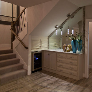 Small contemporary l-shaped wet bar in Kansas City with raised-panel cabinets, beige cabinets, marble worktops, mirror splashback, medium hardwood flooring and brown floors.