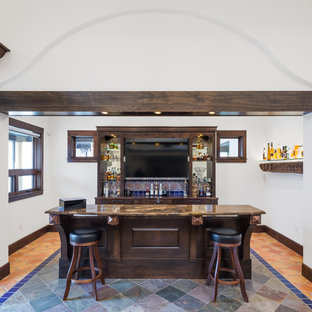 Large tuscan l-shaped slate floor and multicolored floor seated home bar photo in Austin with an undermount sink, shaker cabinets, dark wood cabinets, marble countertops, multicolored backsplash, terra-cotta backsplash and brown countertops