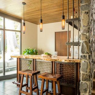 シアトルのラスティックスタイルのおしゃれな着席型バー (オープンシェルフ、木材カウンター、グレーの床) の写真