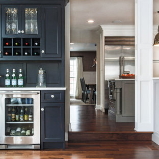 Example of a mid-sized transitional single-wall dark wood floor and brown floor wet bar design in Chicago with recessed-panel cabinets
